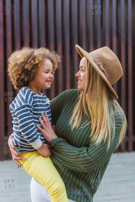 Side view of cheerful young female in trendy sweater and hat embracing cute little daughter while standing on street near modern fence
