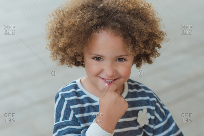 Adorable little girl with curly hair wearing casual striped shirt smiling looking at camera while standing against on the street