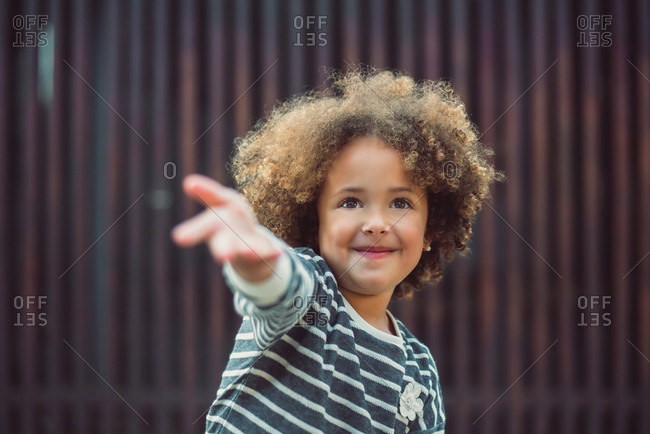 Adorable little girl with curly hair wearing casual striped shirt smiling while standing against blurred wall on street