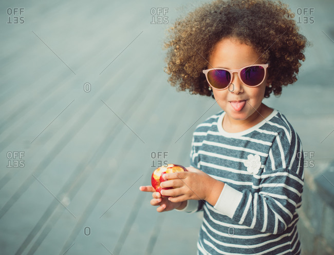 Cute little ethnic girl with Afro hair wearing stylish striped shirt and sunglasses smiling and showing tongue while standing on city street and eating apple