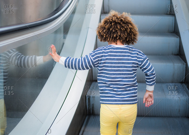 Back view of unrecognizable cute ethnic curly haired girl in trendy outfit standing on stair of escalator in city