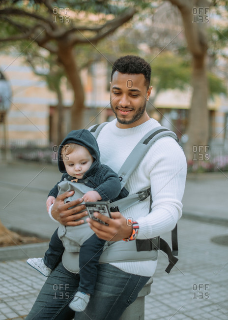Content African American man embracing son in baby carrier while surfing mobile phone on city street