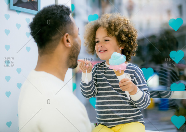 Charming curly ethnic girl holding sweet cone of ice cream playing with black loving father in cafe