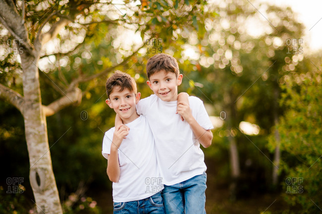 Happy twin boys hugging and looking at camera in park