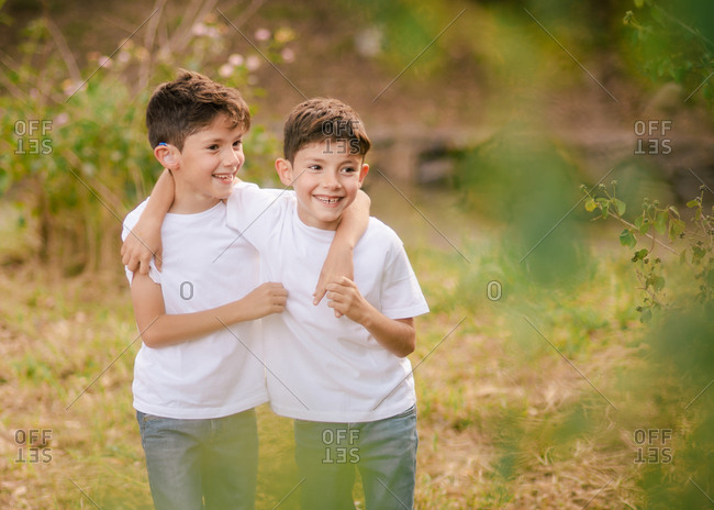 Happy twin boys hugging and looking away in park