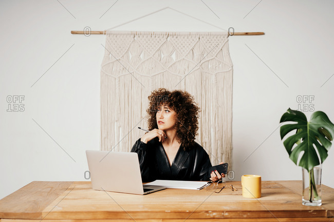 Adult lady in leather jacket and with curly hair sitting at table against macrame decoration and reading data on laptop during work on project in workplace