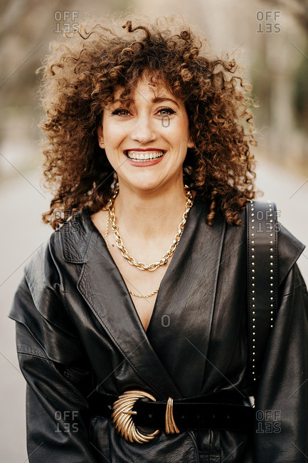 Optimistic female entrepreneur in trendy leather jacket and with curly hair smiling at camera while standing on blurred background of street