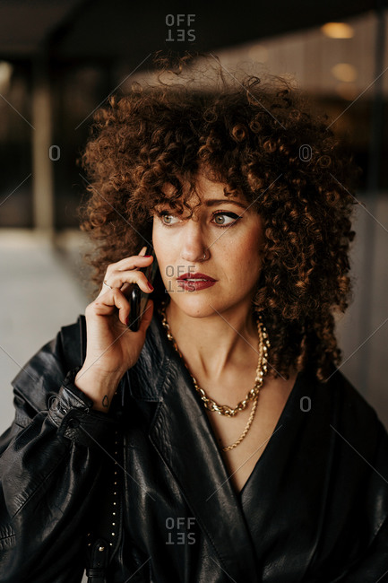 Smart businesswoman in black leather suit and with curly hair looking away and answering phone call while standing near building with glass wall on city street