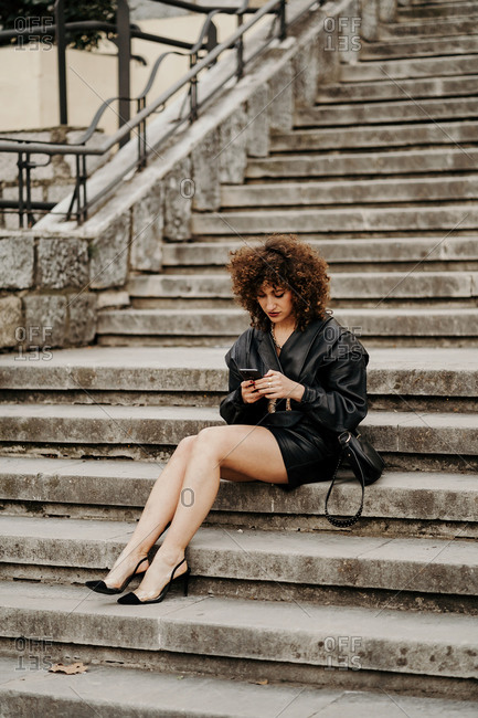 Full length slim female entrepreneur in leather skirt and jacket sitting on concrete steps and browsing smartphone on city street