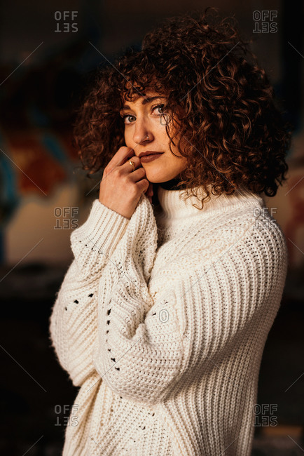 Pleasant curly haired woman with trendy makeup wearing white sweater and looking at camera with hands on face on blurred background