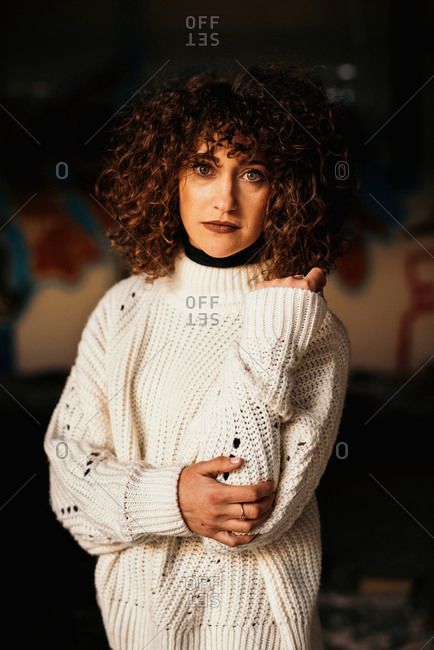 Pleasant curly haired woman with trendy makeup wearing white sweater and looking at camera on blurred background