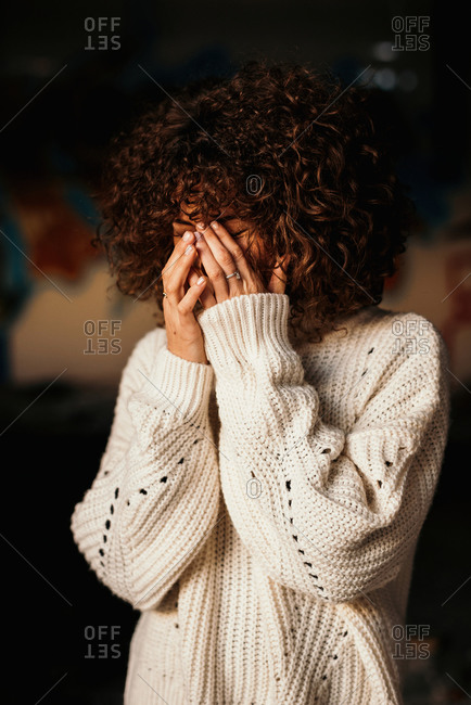 Pleasant curly haired woman with trendy makeup wearing white sweater and smiling with hands on face on blurred background
