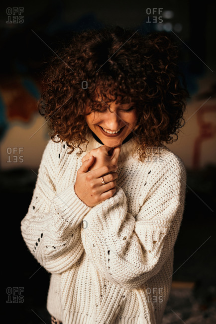 Pleasant curly haired woman with trendy makeup wearing white sweater and looking down on blurred background