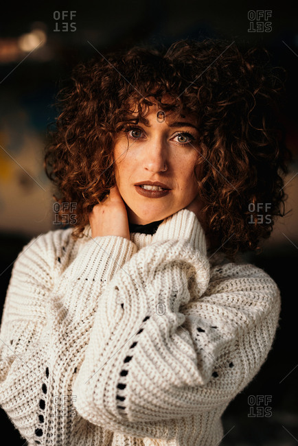 Pleasant curly haired woman with trendy makeup wearing white sweater and looking at camera with hands on neck on blurred background