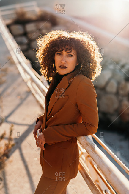 Side view of stylish curly haired woman in trendy outfit looking at camera while leaning elbows on railings at city street on sunny day