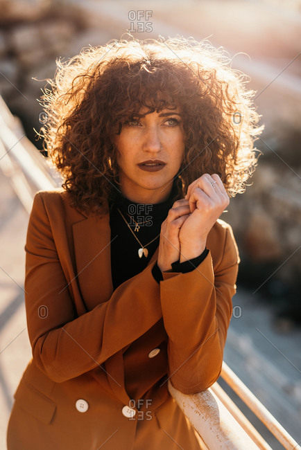 Stylish curly haired woman in trendy outfit looking away while leaning on railings at city street on sunny day