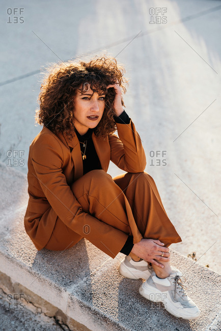 From above of trendy curly haired woman in fashionable ear and sneakers sitting on stone fence and looking at camera at city street