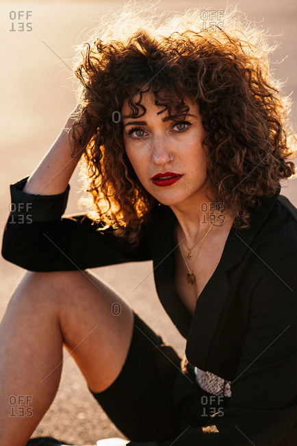 Young woman with curly hair and makeup sitting on asphalt road and looking at camera in sunlight