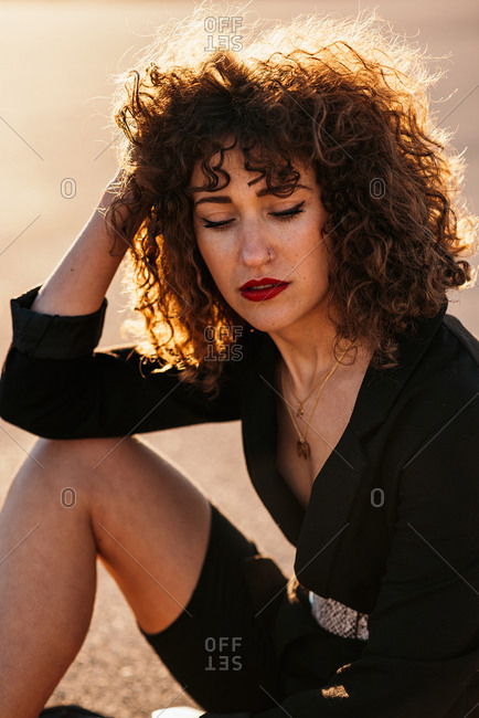 Young woman with curly hair and makeup sitting on asphalt road and looking down in sunlight