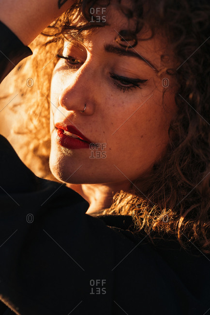 Side view of young woman with curly hair in trendy wear leaning on wall at city street in sunlight on blurred background