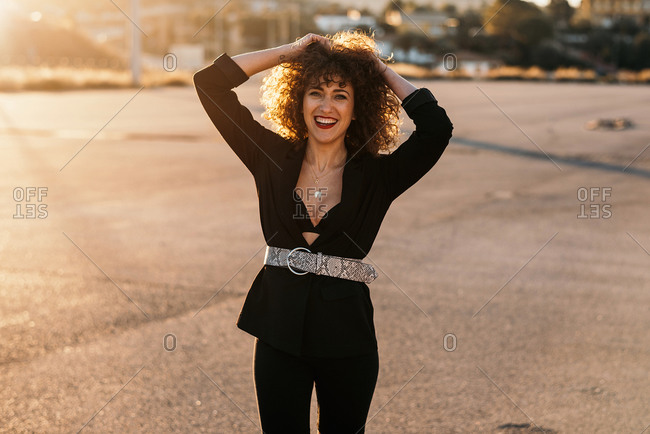 Content curly haired woman in fashionable wear laughing and looking at camera with city street on blurred background