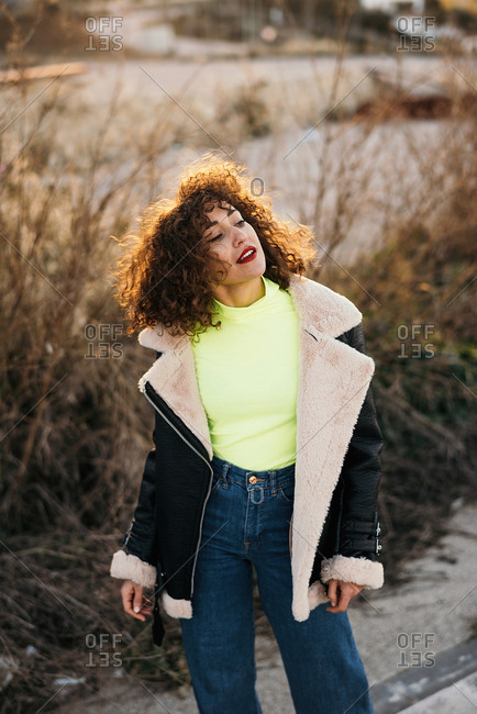 Curly haired young woman in trendy colorful outfit with makeup looking away in spring forest