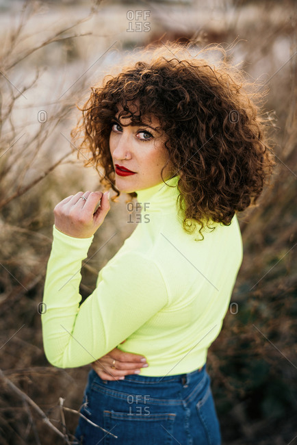 Curly haired young woman in trendy colorful outfit with makeup looking at camera in spring forest