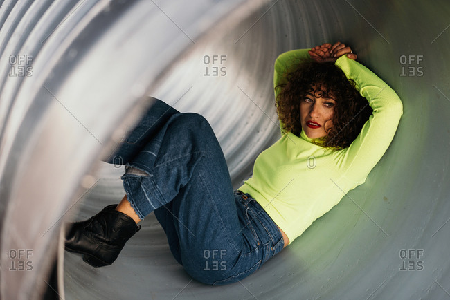 Young woman with curly hair in stylish casual outfit lying in metal big pipe and looking away