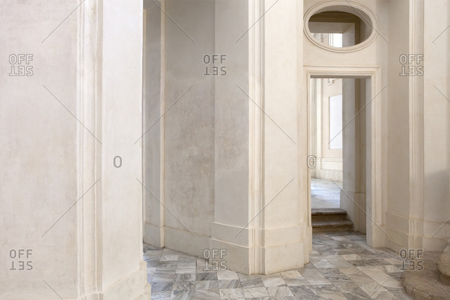 Shabby doorway and hallway inside aged building with ornamental marble walls and tiled floor