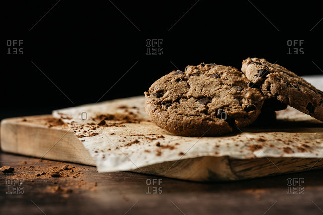 Delicious homemade crispy cookies with chocolate chips served on baking paper on wooden board against black background