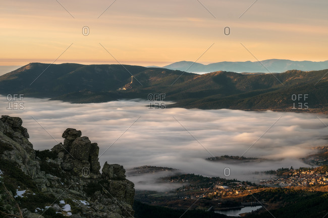 Picturesque drone view of thick white clouds covering valley with town amidst mountains in evening in countryside