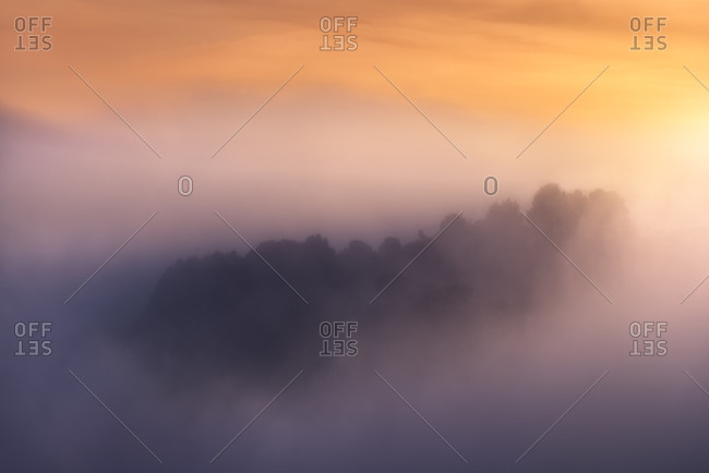 Rough mountain range with trees located against bright sunrise sky in hazy morning in nature
