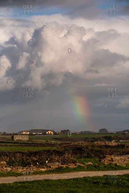 Colorful rainbow shining amidst thick clouds after rain over small settlement in countryside