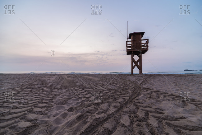 Wooden lifesaver tower located on sandy shore against sunset sky on resort