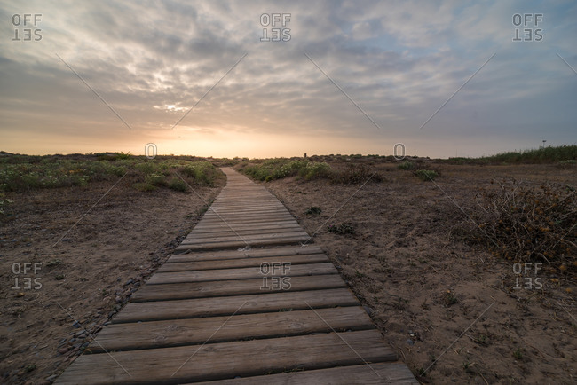 Shabby lumber path going through calm countryside against cloudy sundown sky