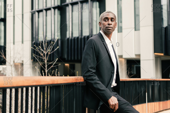 Confident black businessman leaning on railing