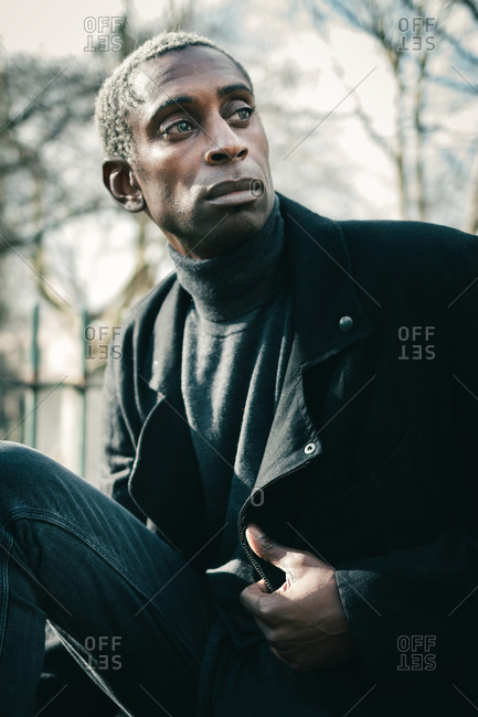 Confident black guy adjusting stylish jacket and looking away while sitting and resting in city park