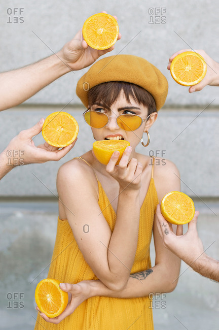 Young female in trendy yellow sunglasses and beret looking away while standing amidst crop unrecognizable people hands with halved oranges against building wall on street of Madrid