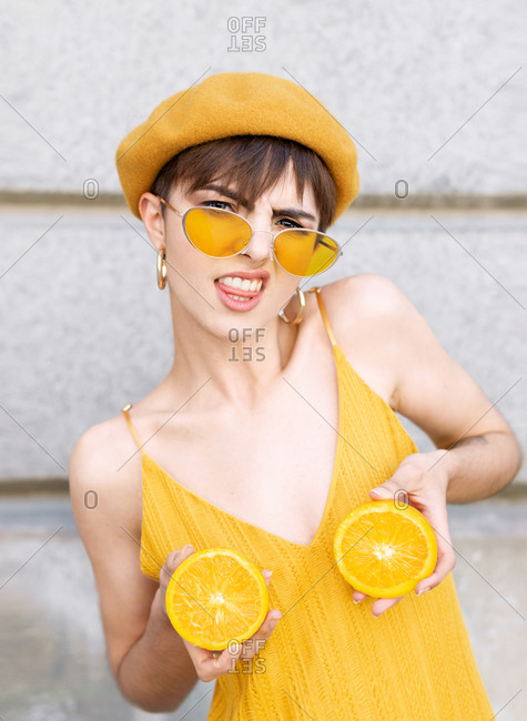 Trendy young female biting tongue and keeping halves of fresh orange near breast while standing against building wall on street of Madrid