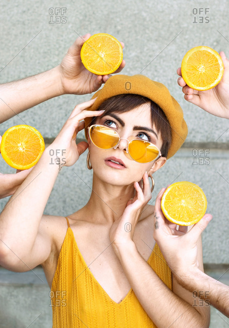 Young female in trendy yellow sunglasses and beret touching face and looking up while standing amidst crop unrecognizable people hands with halved oranges against building wall on street of Madrid
