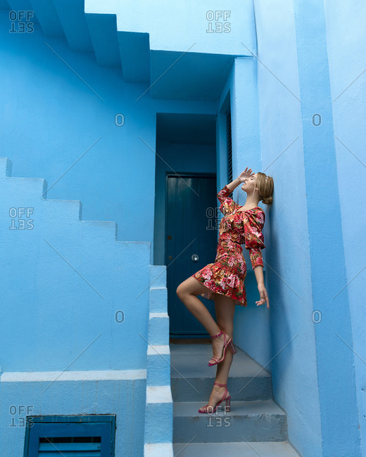 April 13, 2020: From below side view of sensual young fashionable cute blonde woman in stylish colorful dress with closed eyes standing on stairs of blue stone building