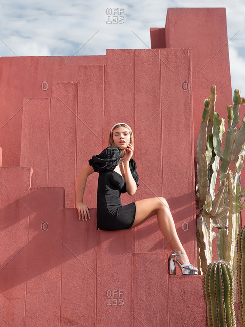 March 25, 2020: From below side view of charming young female in stylish black dress and high heels sitting on stairs of red building near big cactus plant in La Muralla Roja complex and looking at camera in sunny day