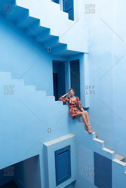 April 13, 2020: Sensual young fashionable cute blonde woman in stylish colorful dress looking at camera while sitting on the edge of stairs of blue stone building