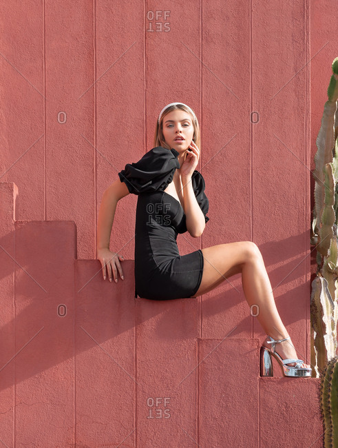 April 2, 2020: From below side view of charming young female in stylish black dress and high heels sitting on stairs of red building near big cactus plant in La Muralla Roja complex and looking at camera in sunny day