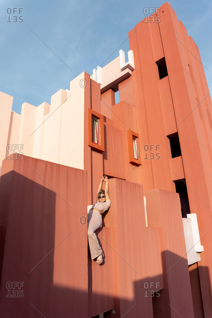 April 13, 2020: From below charming young female in stylish outfit with arms raised leaning and sitting on the edge of stairs of red building in La Muralla Roja complex in sunny day