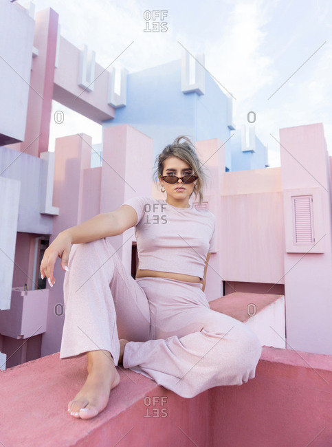 April 13, 2020: blonde woman in stylish outfit with sunglasses looking at camera while sitting on edge of concrete colorful fence of modern pink building in sunny summer day