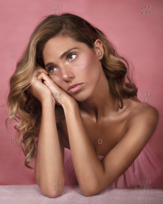 Pretty young woman clasping hands under cheek and looking away while sitting against pink background and dreaming