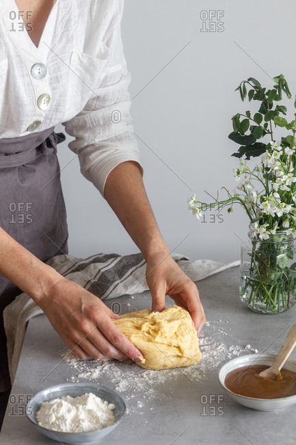 Anonymous female baker in apron kneading soft dough with flour on table near apple sauce and bouquet of flowers while cooking pastry