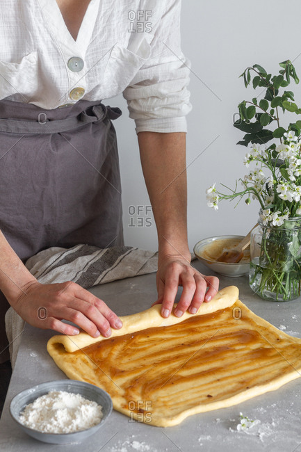 Anonymous woman baker in apron making roll from soft dough with apple sauce on table near flour and bouquet of flowers