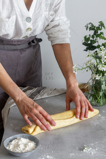 Anonymous woman baker in apron making roll from soft dough on table near flour and bouquet of flowers